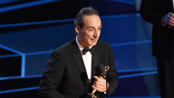 الکساندر دسپلا در هنگام دریافت دومین جایزه اسکارش در نودمین دوره جوایز اسکار